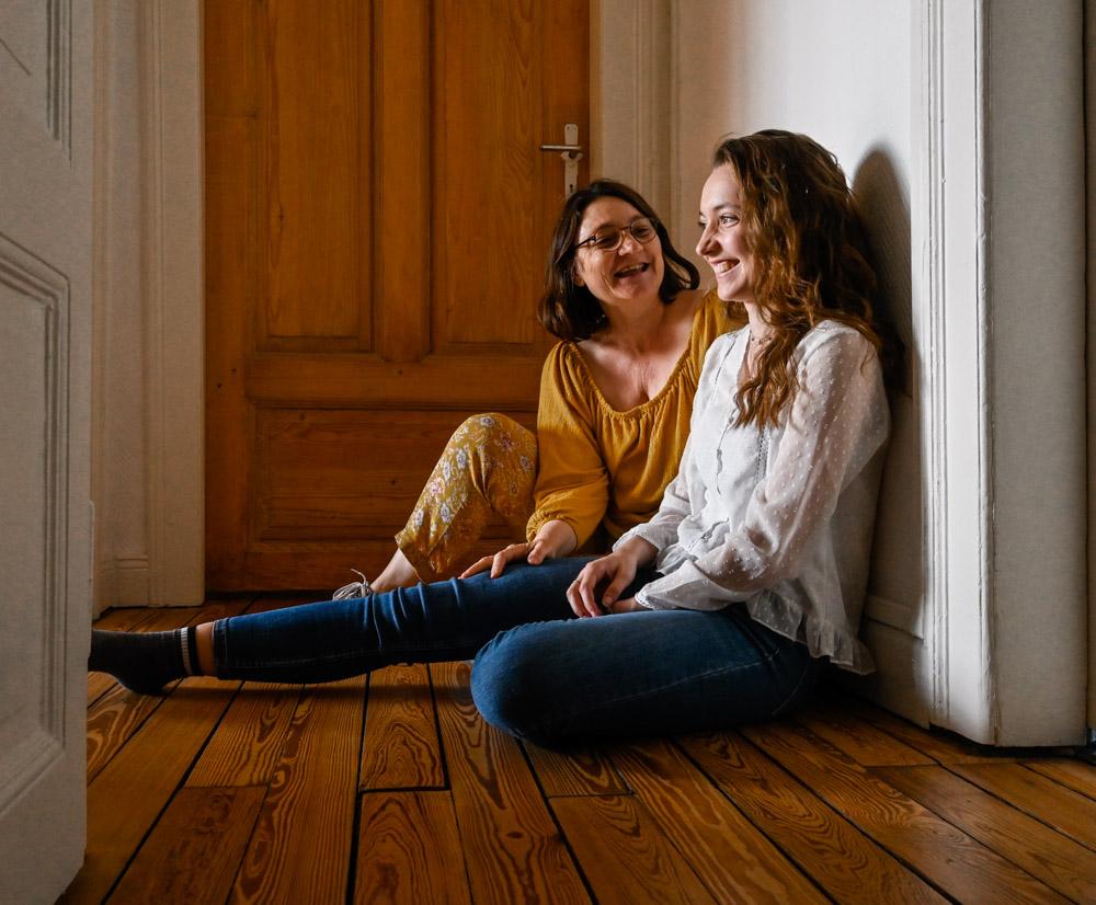 portrait fille et mère assises sur le sol à rire